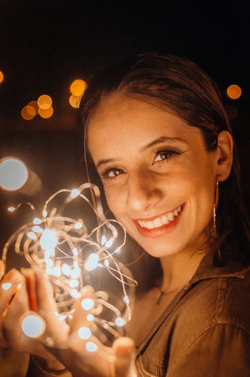 Smiling Woman Holding String Lights