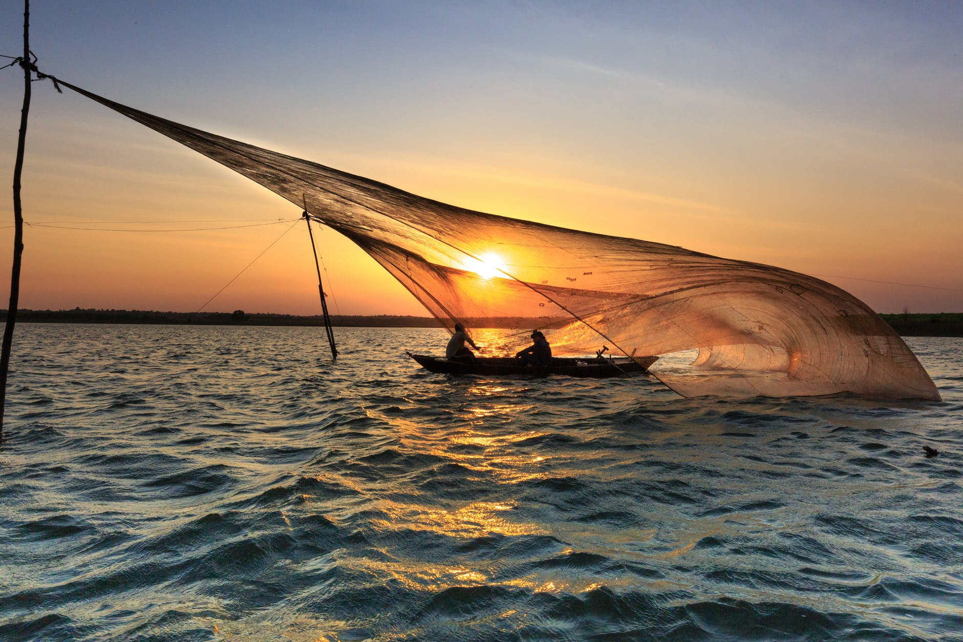 photo of people on a boat during dawn