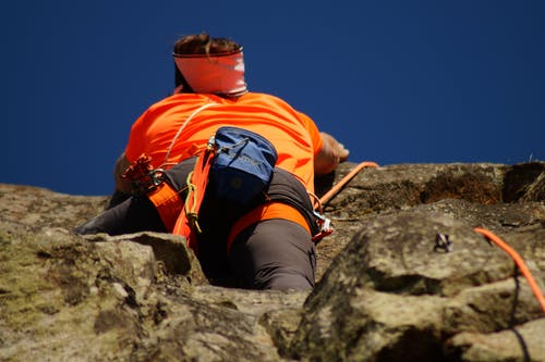 Person in Orange Shirt Climbing Rock during Daytime