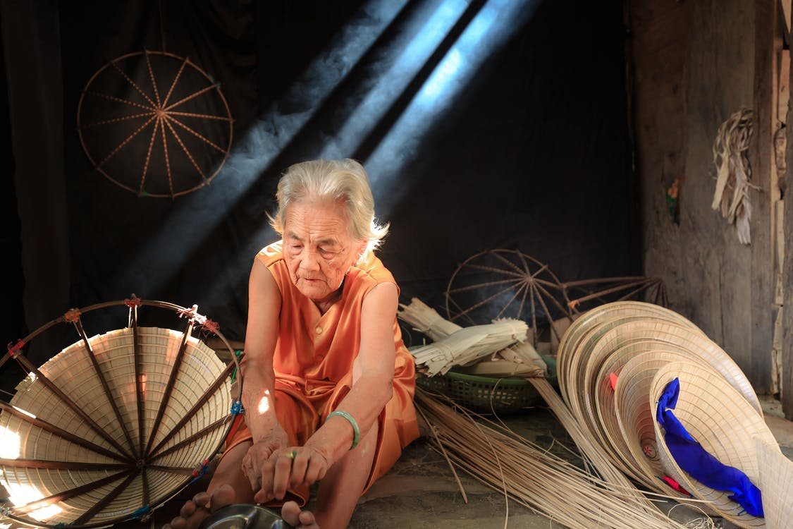 Photo Of An Old Woman Making Straw Hat