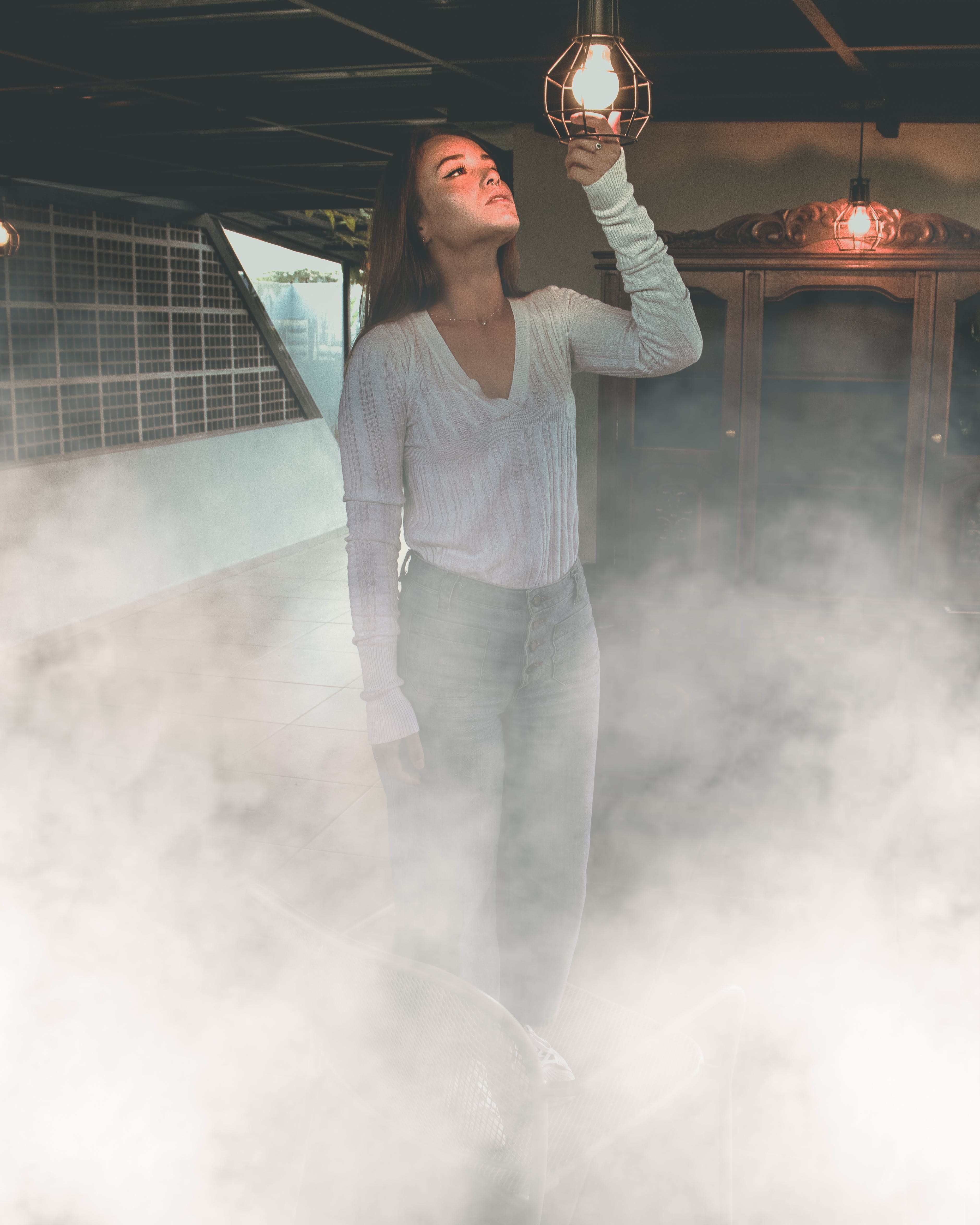 Woman Standing Inside Smoky Room and Holding Turned on Hanging Light Bulb