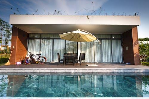 Δωρεάν στοκ φωτογραφιών με αρχιτεκτονική, γυάλινο πλαίσιο, δίπλα στην πισίνα, καρέκλες