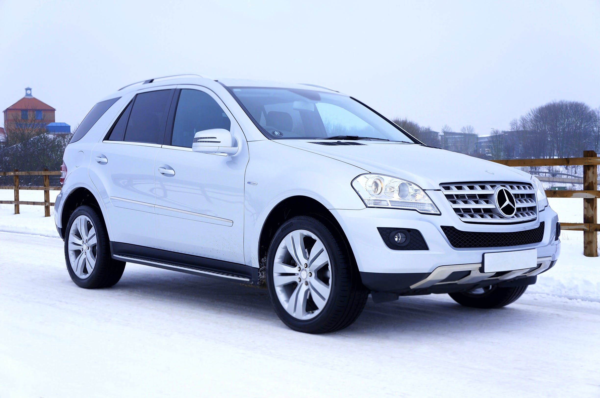White Mercedes-benz Suv Parked Beside Brown Wooden Fence
