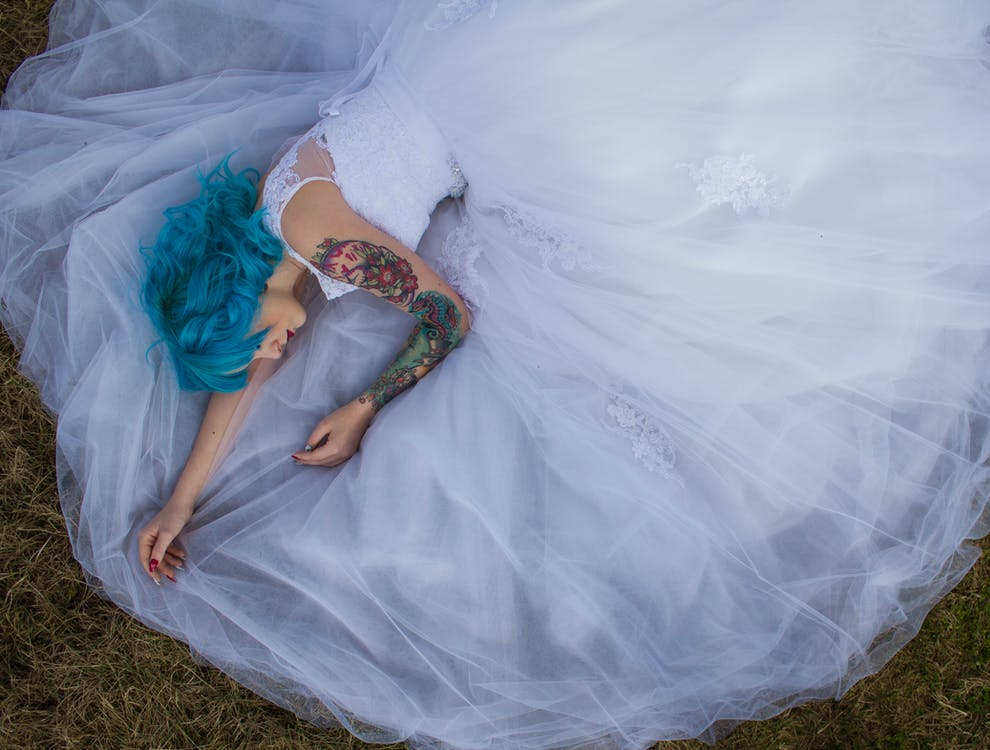 Blue Haired Woman in White Lace Wedding Dress Lying on Green Grasses