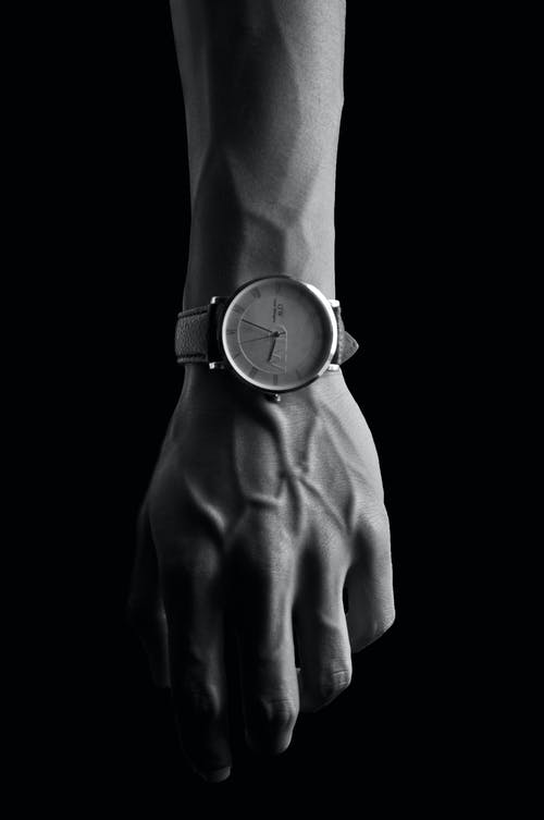 Grayscale Photo of Person Wearing Round Analog Watch