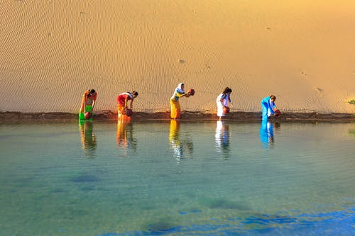 Five Women Getting Water From Body of Water