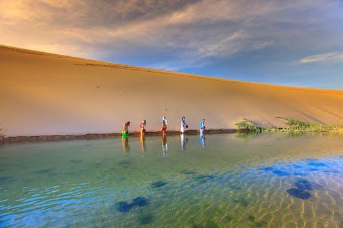 Five Person Standing on Calm Water Near Desert