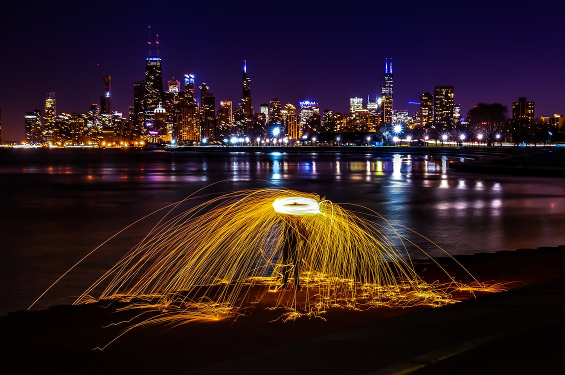 Time-lapse Photography of Person Beside Body of Water Overlooking City Scape