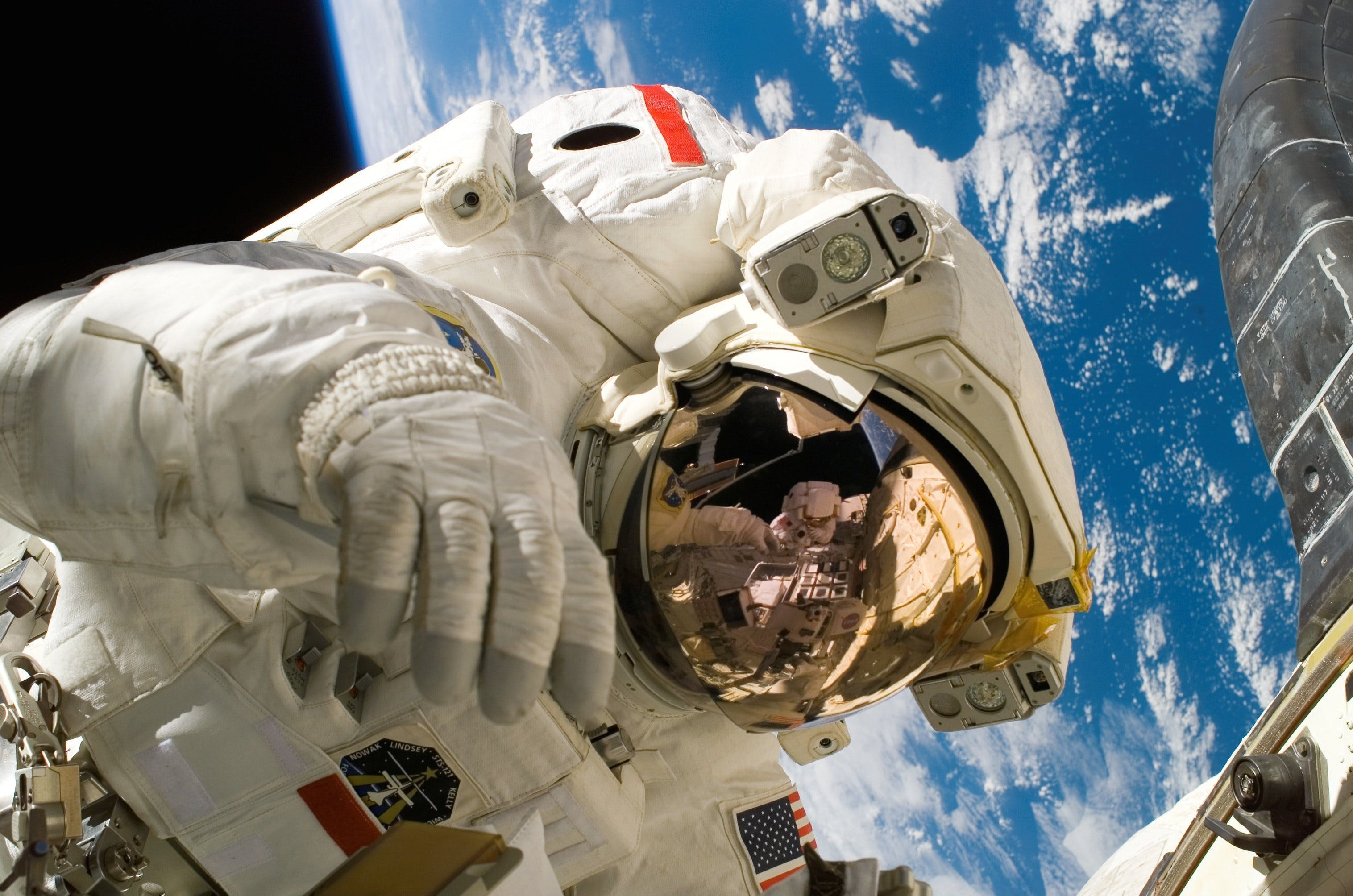 This picture shows an american astronaut in his space and extravehicular activity suite working outside of a spacecraft. In the background parts of a space shuttle are visible. In the far background of the picture planet earth with it's blue color and white clouds is shown as well as a patch of black space.