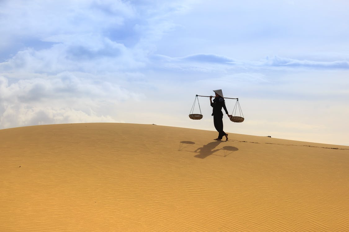 Woman Holding Yoke While Carrying Yoke on Desert