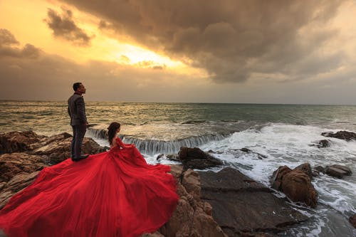 Woman in Red Gown and Man in Gray Suit Standing and Sitting on Boulders in Front of Ocean