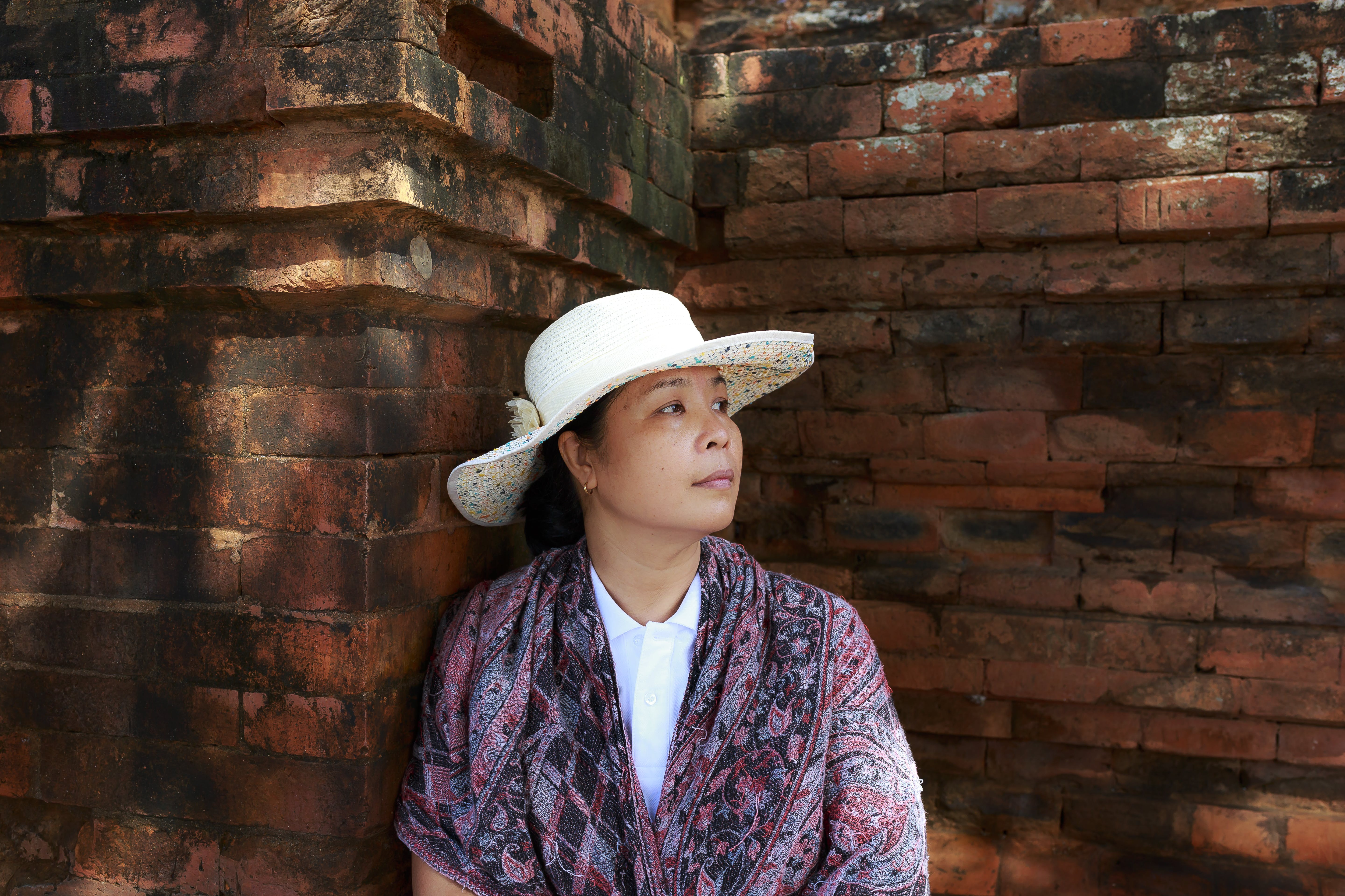 Woman Wearing White Hat Leaning on Brown Wall