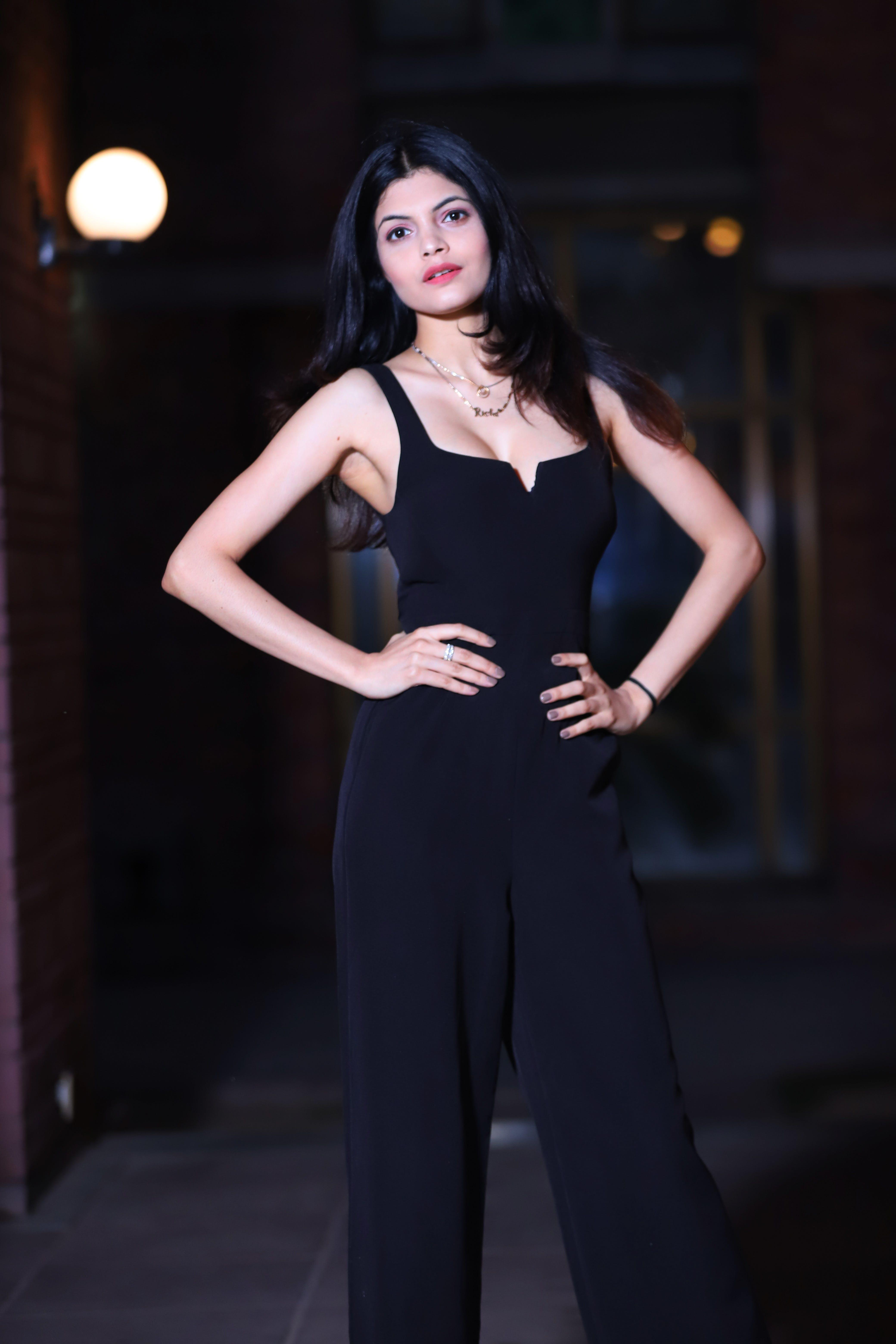 Standing Woman Wearing Black Tank Overalls