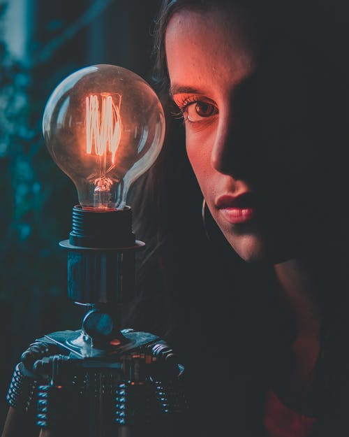 Selective Focus Photography Of Woman Beside Bulb