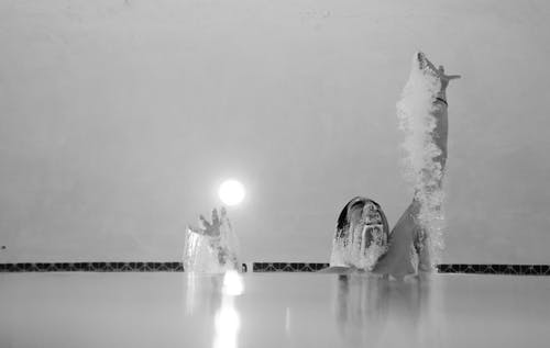 Grayscale Photo of Person in Swimming Pool