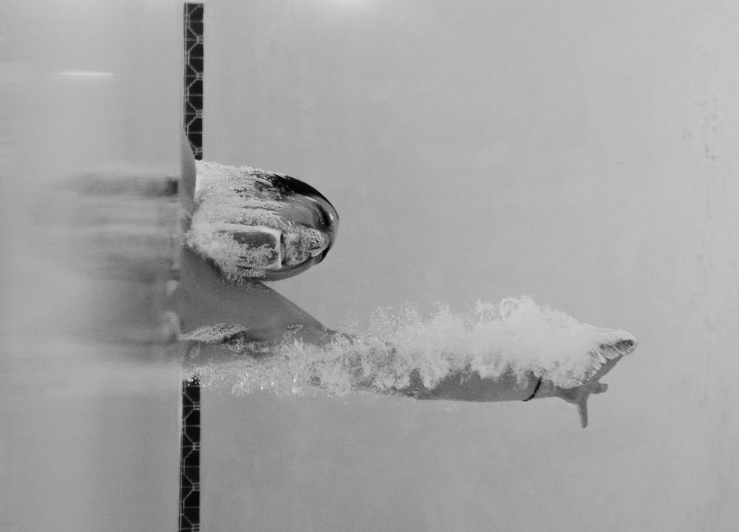 Person Swimming at the Pool in Grayscale Photo