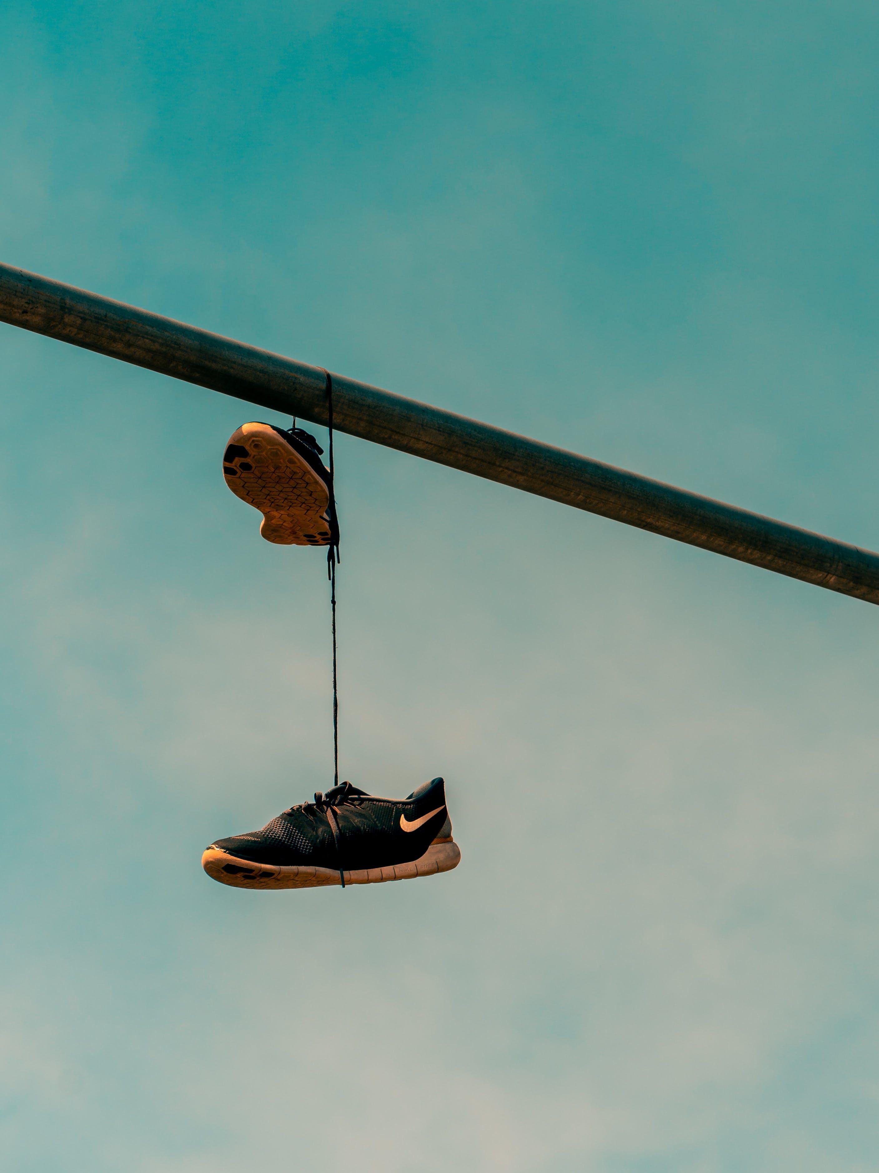 Black Nike Sneakers Hanged on Gray Metal Bar