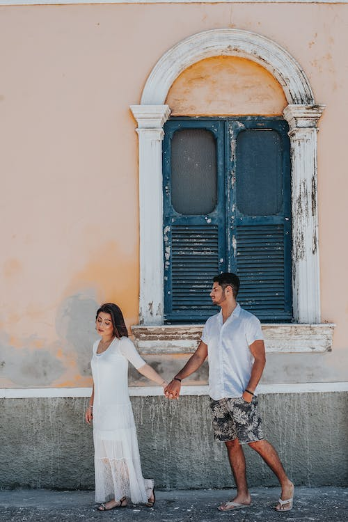 Man And Woman Holding Hands Near Wall