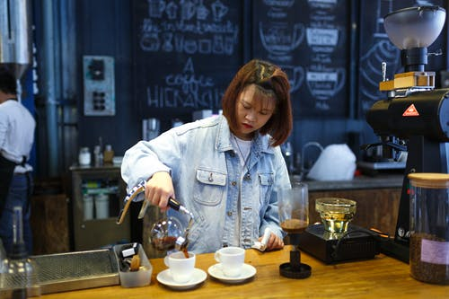 Woman Pouring Coffee on Cup