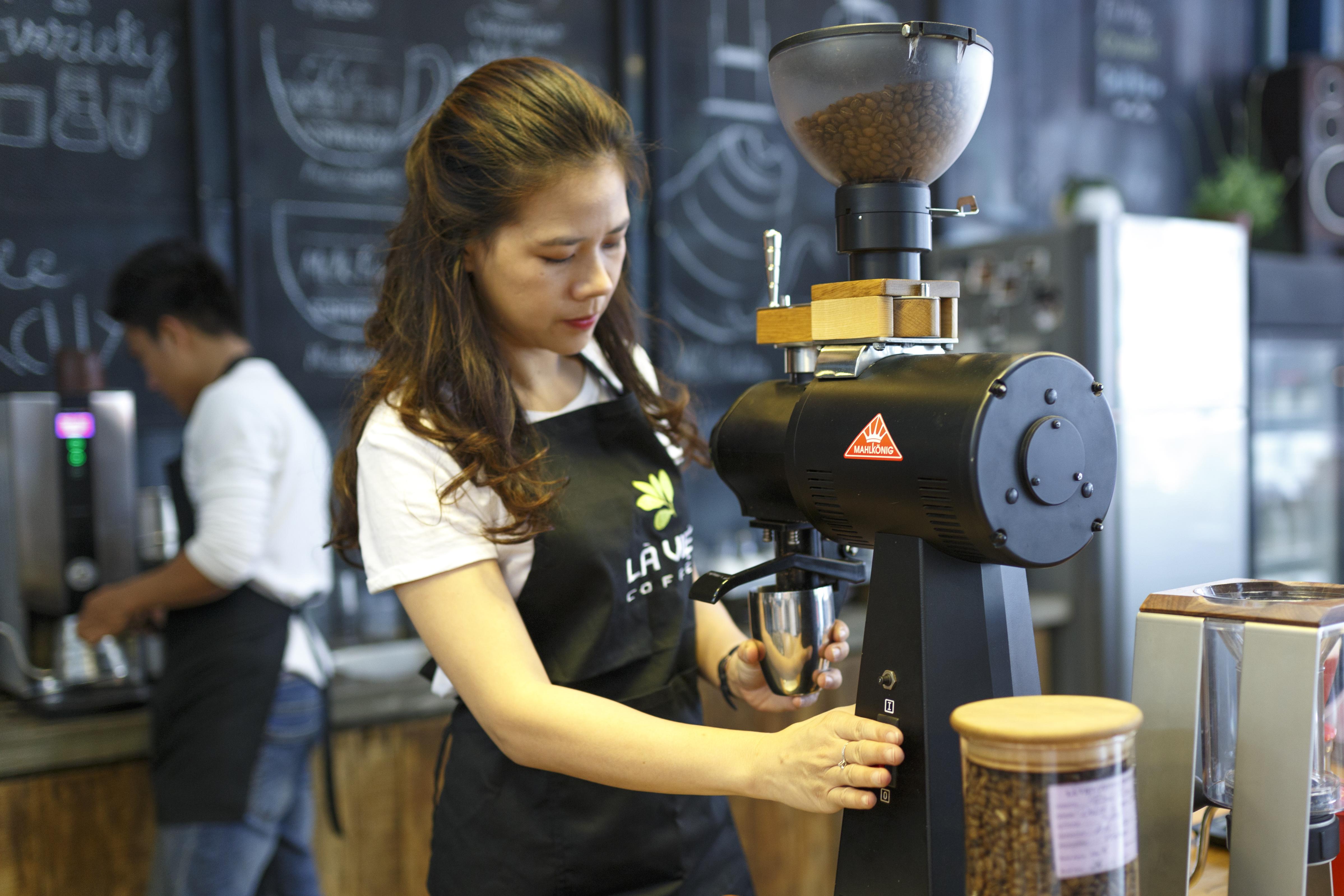 Woman Grinding Coffee Bean