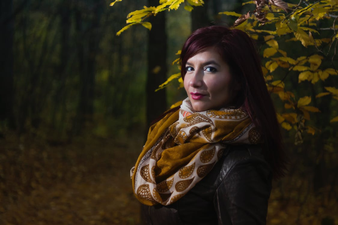 Woman Wearing Brown and White Scarf Surrounded by Trees at Daytime