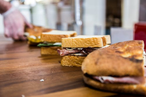 Lined Up Sandwiches on Brown Wooden Table