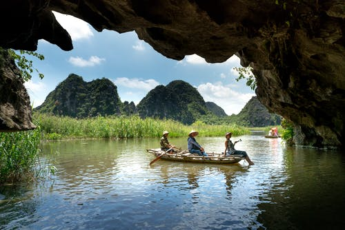 Three People Sitting on Boat While Sailing Under Cave