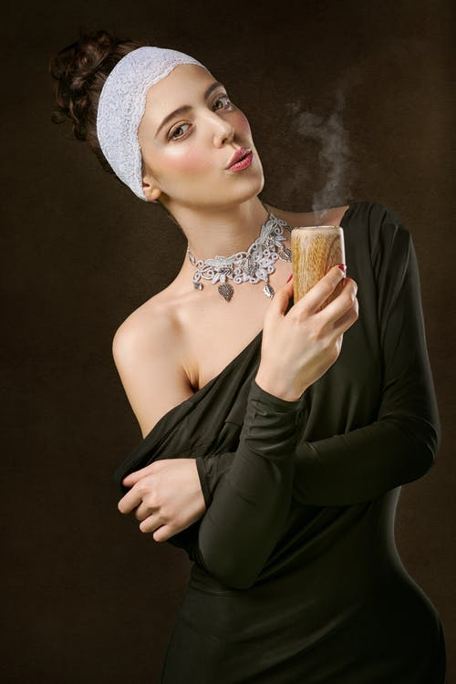 Photo of Woman Holding a Blown Out Candle Posing