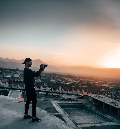 Бесплатное стоковое фото с город, закат, мужчина, небо