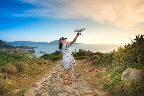 Photo of a Woman Holding a Drone