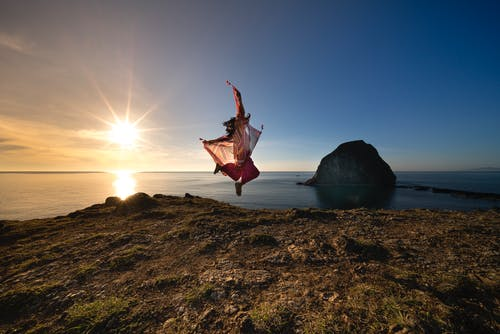 Persona Saltando Sobre La Orilla Rocosa