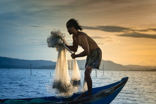 Man Casting White Net At Sea