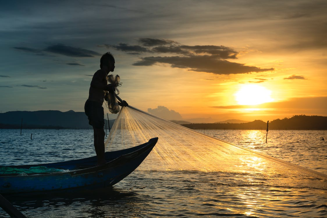Silhouette Of Man On Boat Fishing On Body Of Water