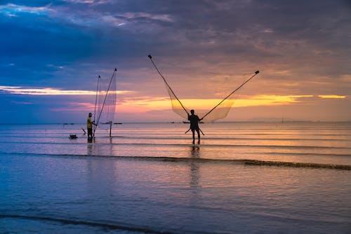 Photo of Two Men Holding Nets in Ocean