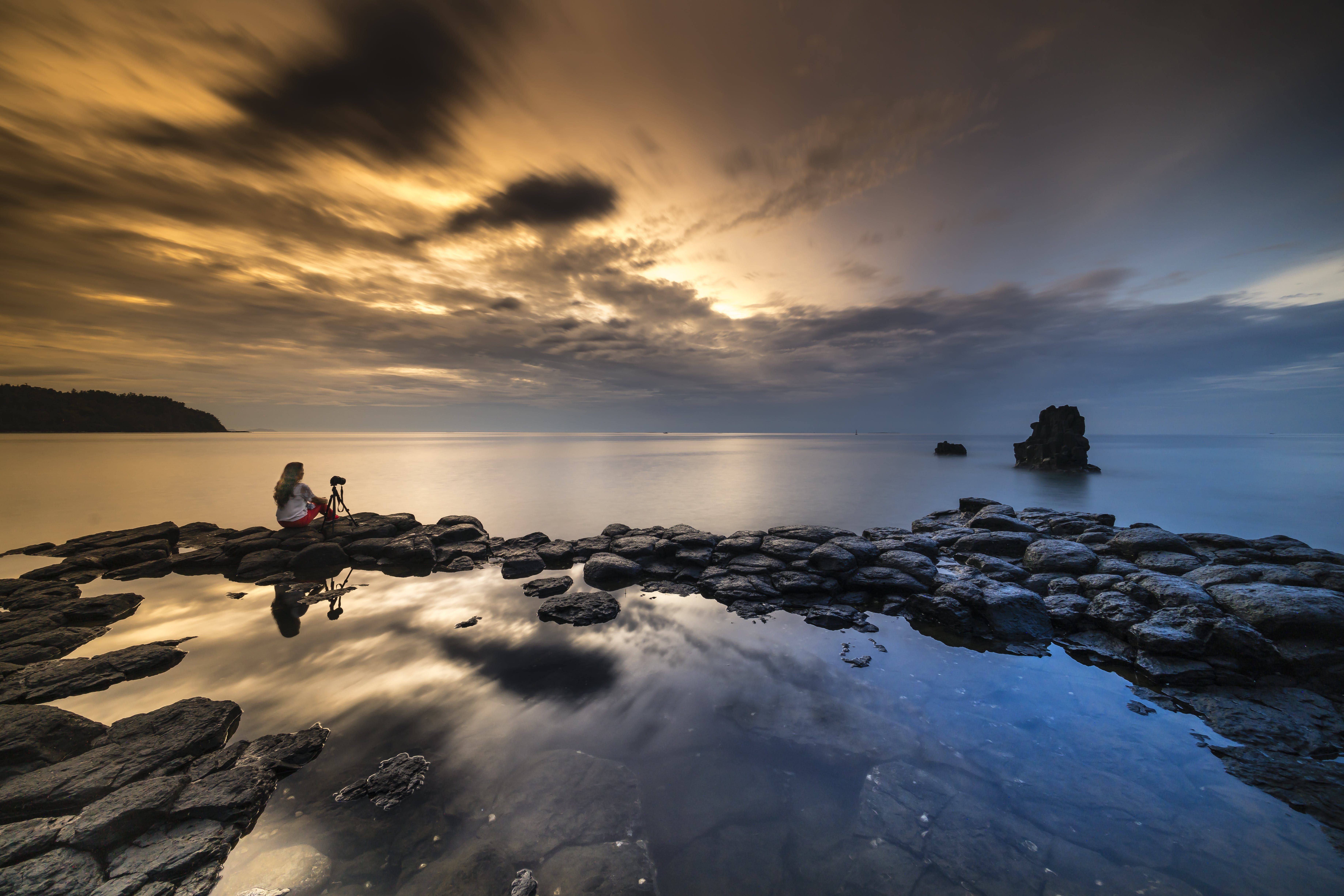 Person Sitting On Stone While Facing The Calm Sea During Sunset