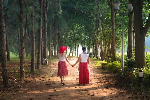 Foto stok gratis bergandengan tangan, berjalan, berpegangan tangan, di luar rumah