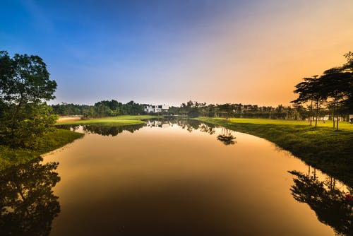 Calm Body Of Water Surrounded By Green Grass Field During Sunset