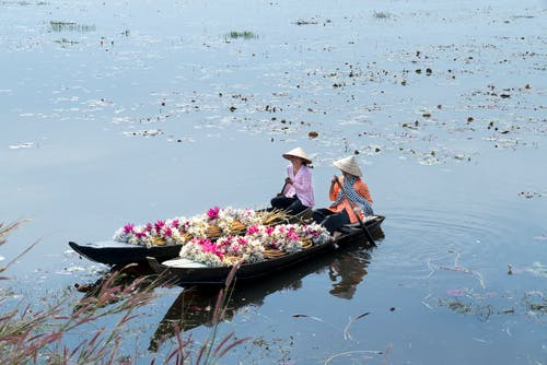 Photo of Two Women Riding Canoes With Flowers