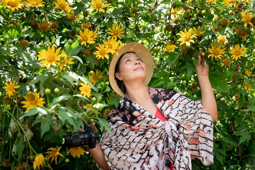 Photo of Woman Near Yellow Flowers
