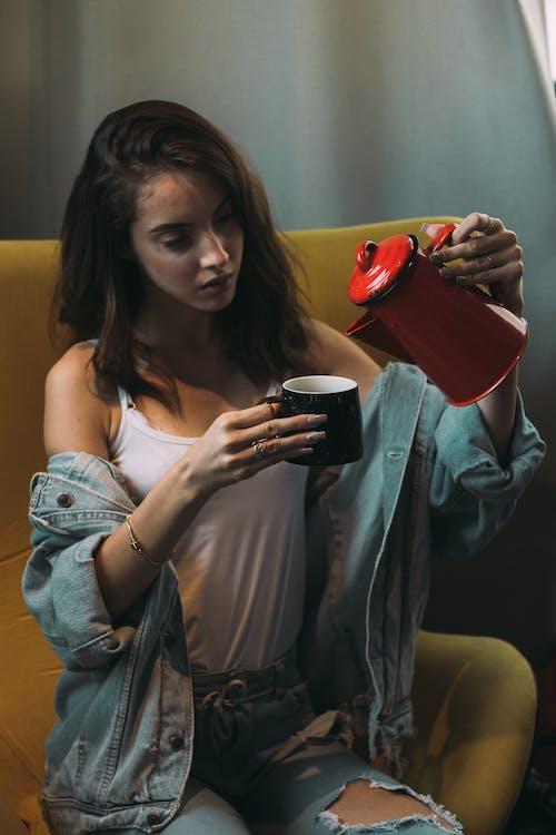 Woman Wearing White Tank Top Pouring Coffee on Mug