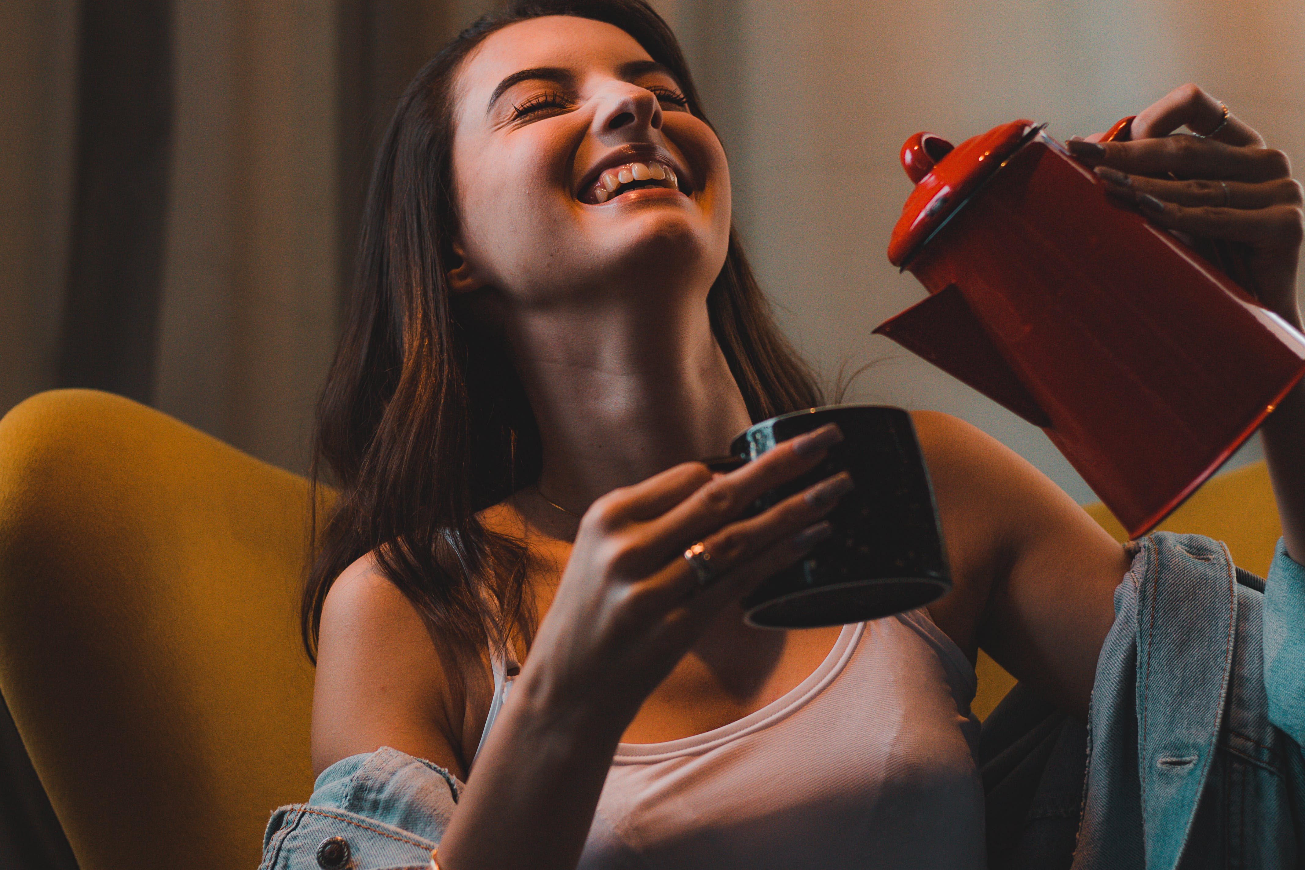 Woman Smiling While Pouring Beverage On Mug