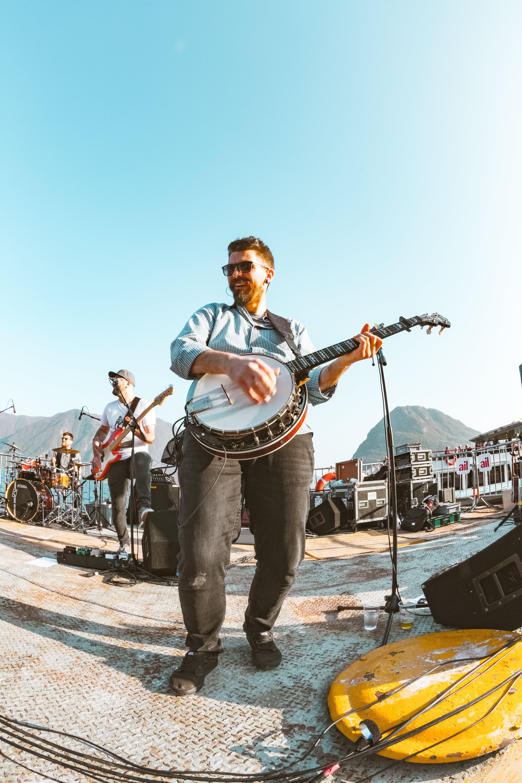 Smiling Man Playing Banjo Near Another Man Playing Guitar