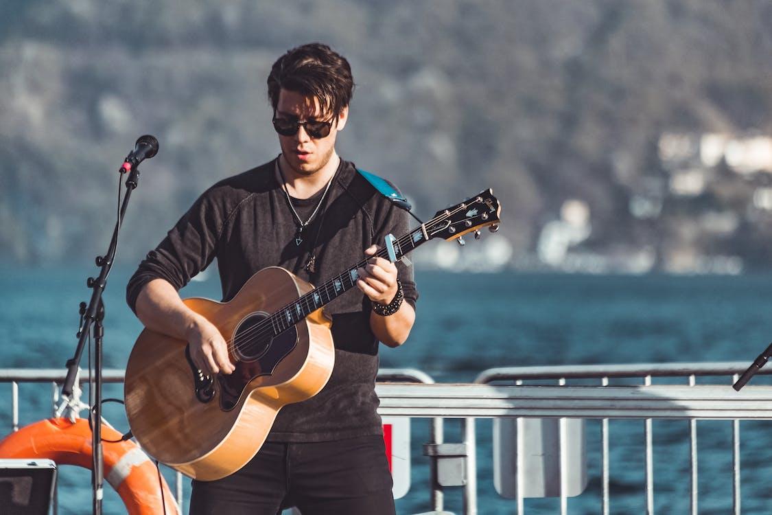Man in Black Long-sleeved Shirt Playing Brown Acoustic Guitar