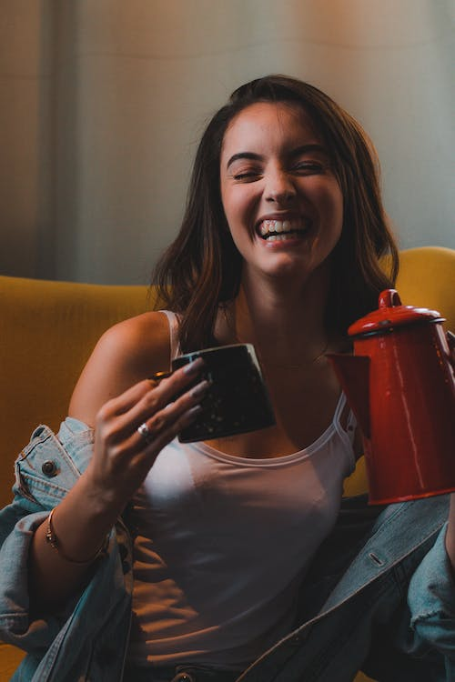 Photo of Laughing Woman While Holding Mug and Kettle