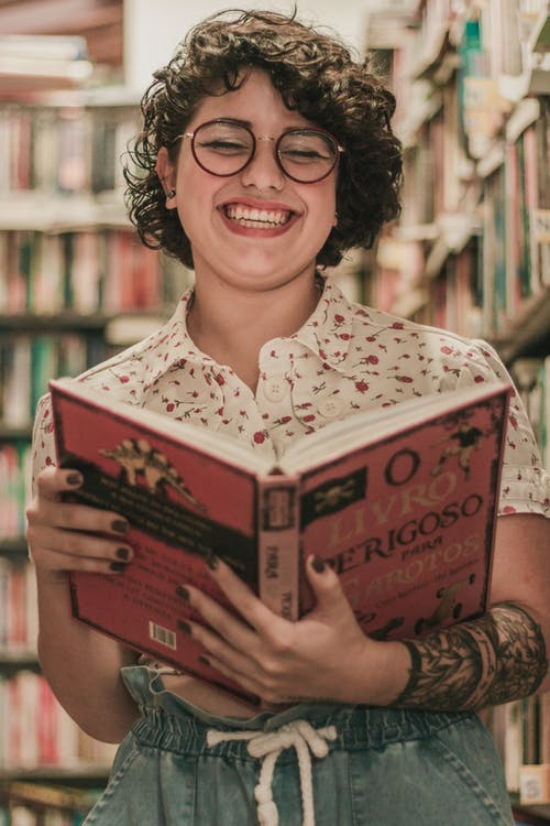 Woman Smiling While Holding Opened Book