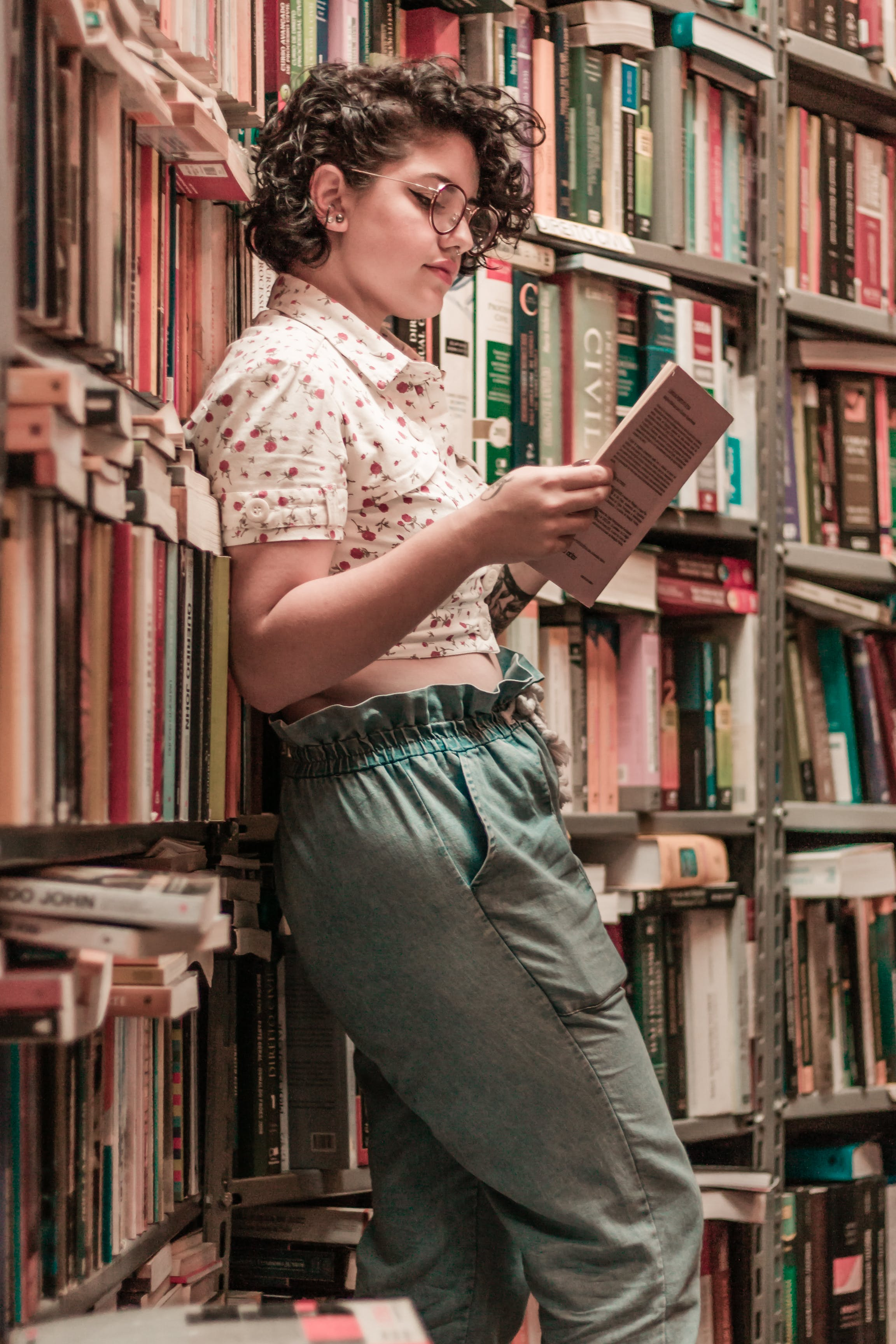 Woman Holding Book Leaning on Books on Shelves