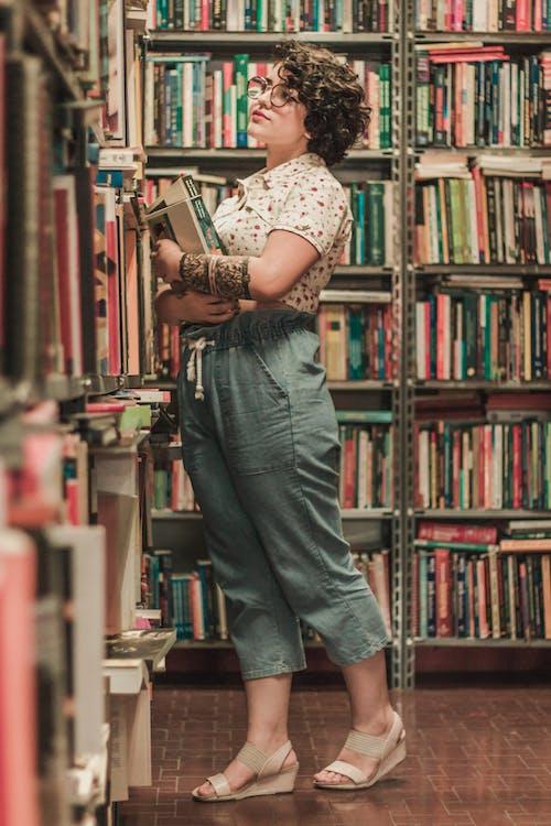 Бесплатное стоковое фото с вид сбоку, вьющиеся волосы, женщина, книжный магазин