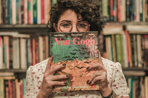 Shallow Focus Photo of a Woman Holding Van Gogh Book