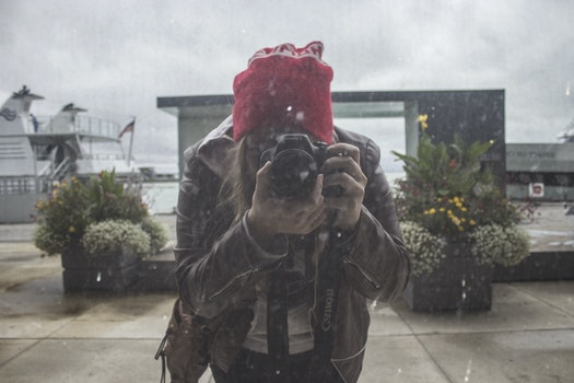 Woman in Brown Leather Jacket and Red Knit Cap Using Black Dslr Camera