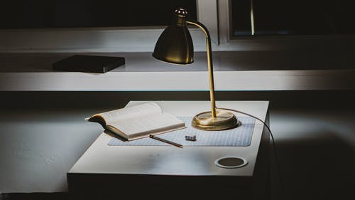 Powered-on Gold Desk Lamp on Desk With Opened Book
